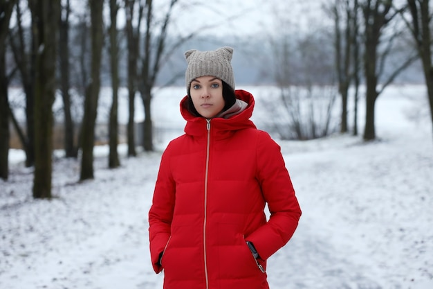 Una giovane ragazza con un lungo cappotto rosso imbottito si trova nella foresta invernale. Foto Premium