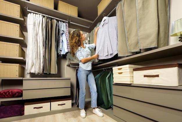 Ragazza giovane guardando i vestiti in una cabina armadio o guardaroba rimuovendo una maglietta dal rack per uno sguardo più attento