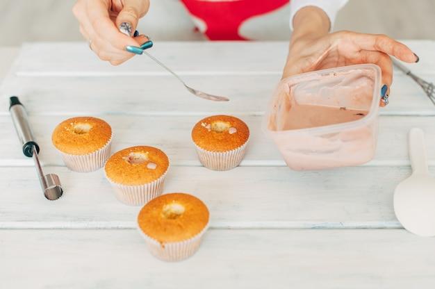 La ragazza fa deliziosi cupcakes teneri.