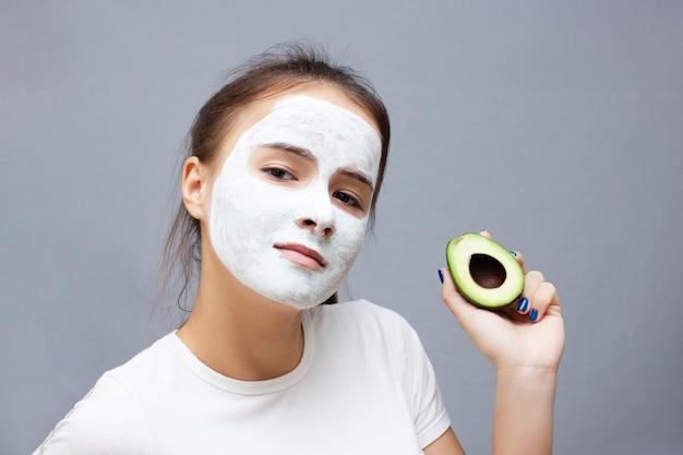 La ragazza fa una maschera per il viso detergente idratante