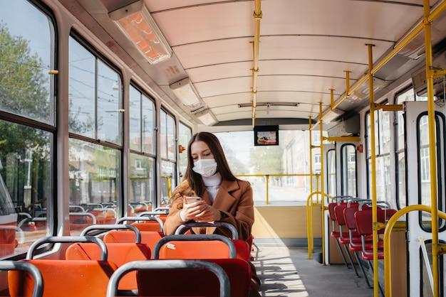 Una ragazza con una maschera usa i mezzi pubblici da sola, durante una pandemia. protezione e prevenzione covid 19.