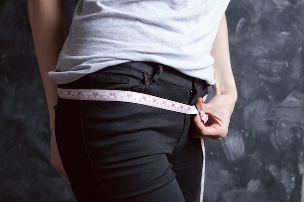 Ragazza che misura la sua vita con un metro a nastro