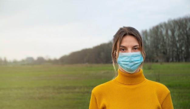 Giovane ragazza in una maschera medica nel parco a causa dell'inquinamento atmosferico o di un'epidemia di virus.