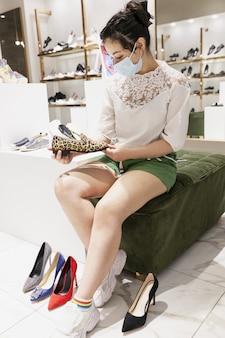 Giovane ragazza in una maschera medica in un negozio di scarpe. grande scelta.