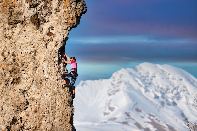 Una giovane ragazza alpinista durante una scalata