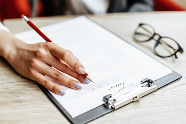 L'impiegato di concetto della ragazza o la signora di affari firma i documenti. donna di affari concentrata che lavora con le carte. concetto di affari