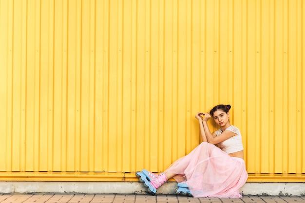 La ragazza in gonna rosa e pattini a rotelle si siede sul marciapiede contro il fondo giallo della parete e le mani fa il cuore
