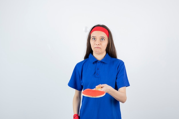 Una giovane ragazza che gioca a ping pong con racchetta e palla.