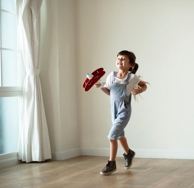 Ragazza che gioca con un aereo giocattolo Foto Premium