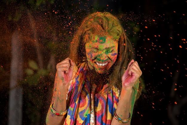 Una giovane ragazza gioca con i colori. il concetto per il festival indiano holi. spruzzi di colore.