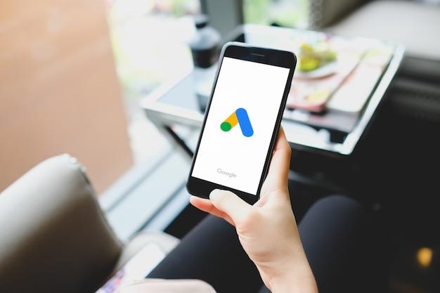 Ragazza che punta su annunci google sullo schermo dello smartphone durante una prevenzione pandemica e coronavirus. google ads è una piattaforma online per la pubblicità, l'offerta di servizi.