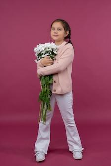 Una giovane ragazza posa su uno sfondo rosa con fiori tra le mani crisantemo