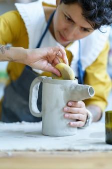 Giovane ragazza artista della ceramica che modella brocca da argilla grezza con spugna bagnata artigianato femminile laboratorio d'arte donna