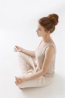 Ragazza giovane pratica yoga su sfondo bianco. ritratto di donna caucasica splendida dei capelli rossi che fa