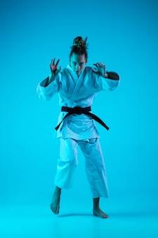 Judoist professionista della giovane ragazza isolato sul fondo blu dello studio in neon