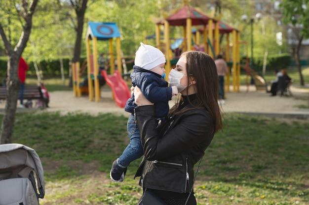 La ragazza in una maschera protettiva bacia il suo piccolo bambino. covid-19