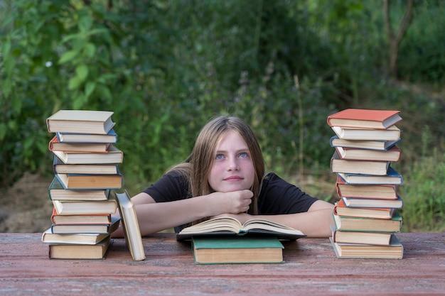 Giovane ragazza che legge un libro e sogna in giardino a un tavolo di legno con una pila di libri. concetto di educazione domestica
