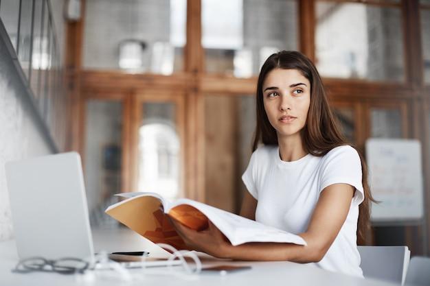 Ragazza che legge un libro e utilizza un computer notebook per acquisire conoscenze in un luminoso caffè concetto di educazione.