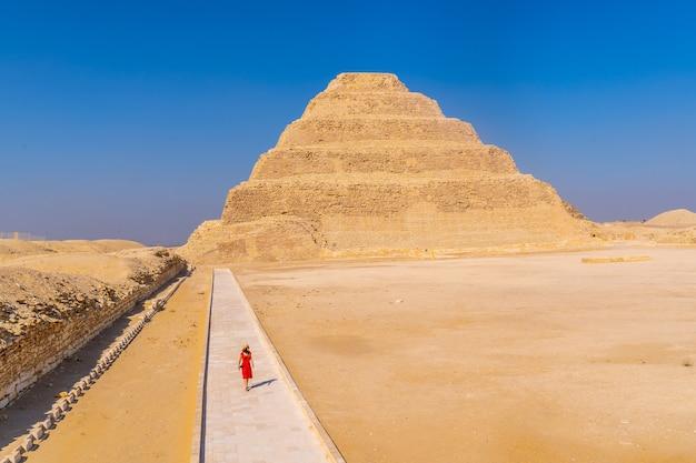 Una giovane ragazza in un vestito rosso che cammina nella piramide a gradini di djoser, saqqara. egitto. la necropoli più importante di menfi. la prima piramide al mondo