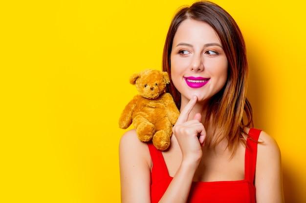 Giovane ragazza in abito rosso con orsacchiotto di peluche sulla sua spalla gialla