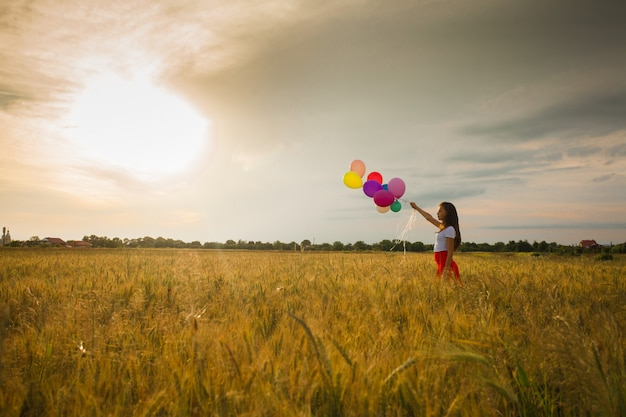 Giovane ragazza in una gonna rossa in esecuzione con palloncini colorati nel campo di grano. ispirazione alla natura, retroilluminazione