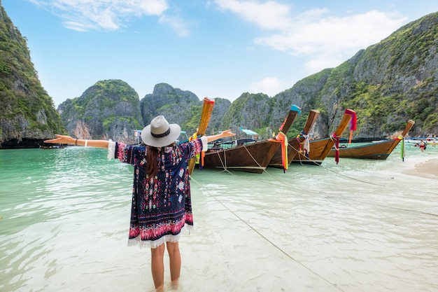 Ragazza giovane rinfrescante con barche in legno a coda lunga a maya bay, krabi, thailand