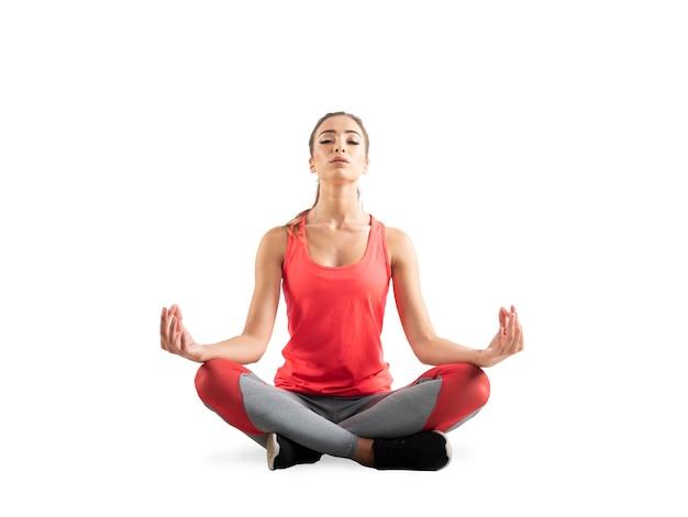 Ragazza che si distende nella posizione di yoga isolata sulla superficie bianca