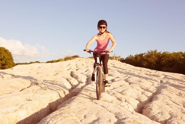La ragazza guida la sua bici giù per la collina.
