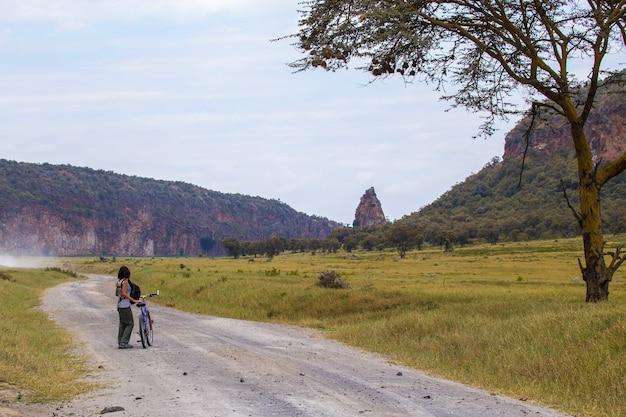 Una giovane ragazza in sella a una bicicletta nel parco nazionale di naivasha hell's gate pieno di animali. kenya walking o bike safari