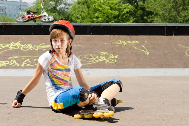 Giovane ragazza in rollerblades seduto sull'asfalto