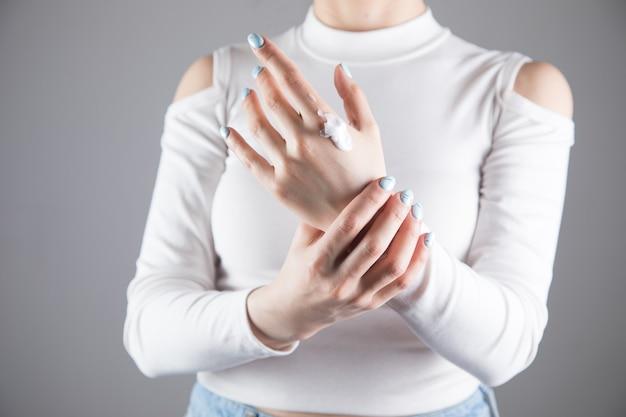 La ragazza si strofina le mani con la crema su una scena grigia