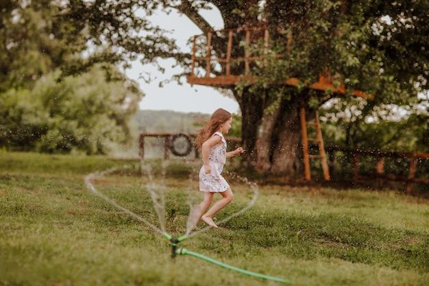 Ragazza che passa l'acqua di spruzzatura sulla radura verde