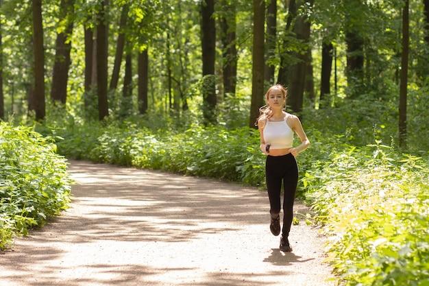 La ragazza corre nel parco, fa sport all'aperto