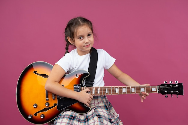 Una giovane ragazza in uniforme scolastica suona una chitarra elettrica