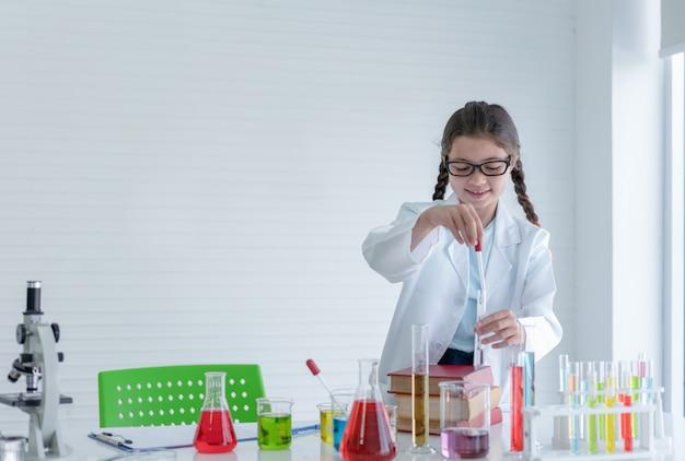 Scienziato della ragazza che fa esperimenti chimici nel tubo di vetro nella stanza del laboratorio