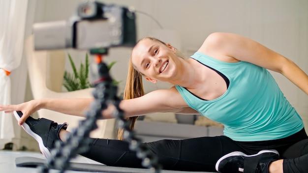 La ragazza che riprende il suo videoblog di fitness la ragazza conduce l'insegnamento a distanza all'allenamento online