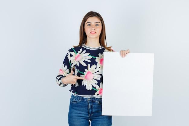 Giovane ragazza che mostra poster di carta in camicetta floreale, jeans e guardando perplesso, vista frontale.