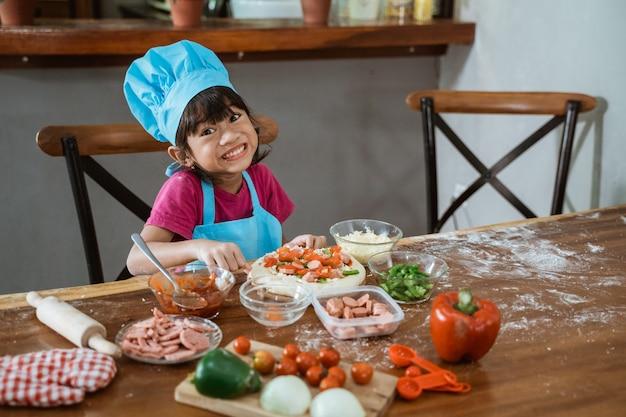 La ragazza mostra una pizza sul tavolo in cucina