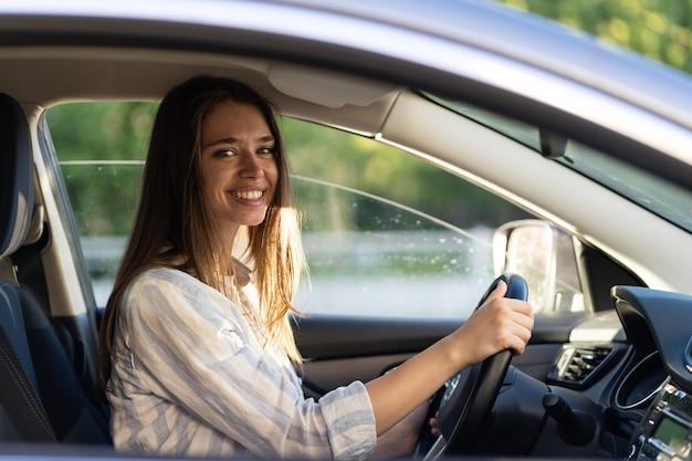 La ragazza si siede al sedile del conducente in una nuova auto sorridendo si tiene per mano sul volante felice di ottenere la patente di guida