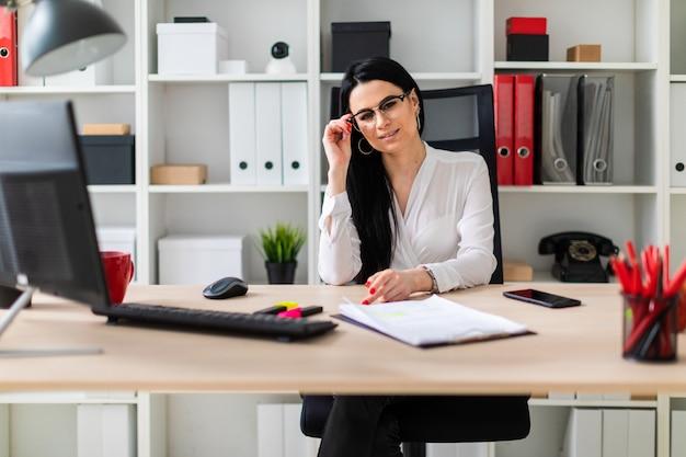 Una ragazza si siede alla scrivania di un computer e tiene una mano sul ceppo di occhiali.