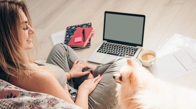 Una giovane ragazza si siede sul pavimento con il suo cane pomerania e lavora su un laptop. il cane la sta guardando