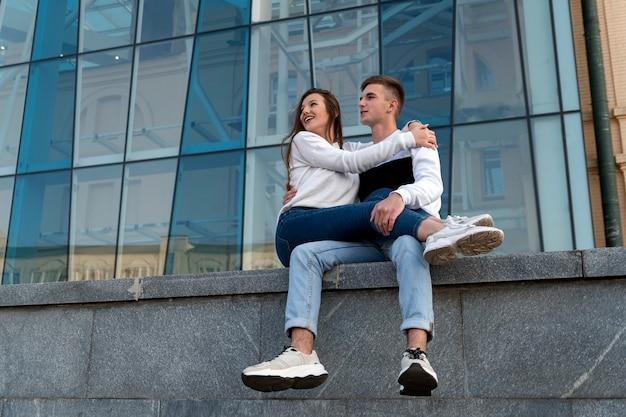 La ragazza si siede sulle ginocchia del suo ragazzo. elegante giovane coppia abbracci e riposo in città. vista dal basso.