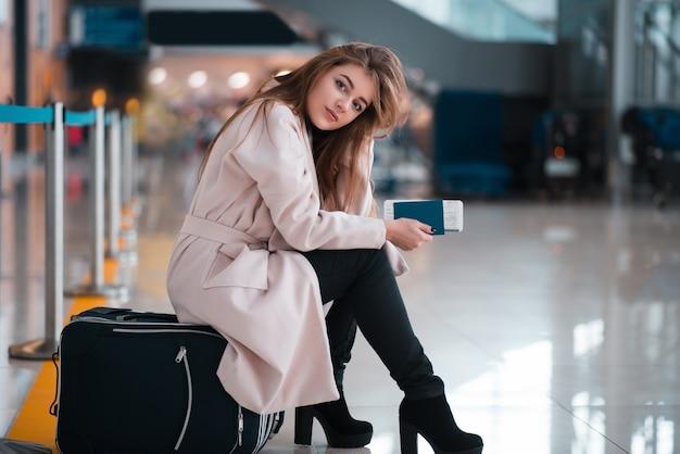 La ragazza si siede su una valigia in aeroporto.