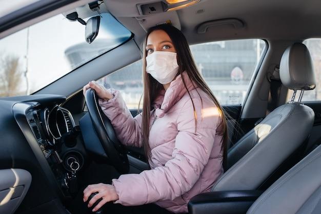 Una giovane ragazza si siede al volante in macchina con la maschera durante la pandemia globale e il coronavirus. quarantena.