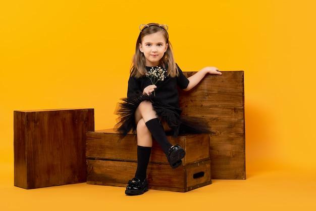 Ragazza che si siede fra le scatole di mele di legno sulla parete arancio