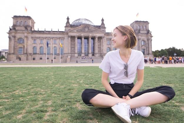 Giovane ragazza seduta sullo sfondo di un edificio storico e sorridente viaggiatore a berlino