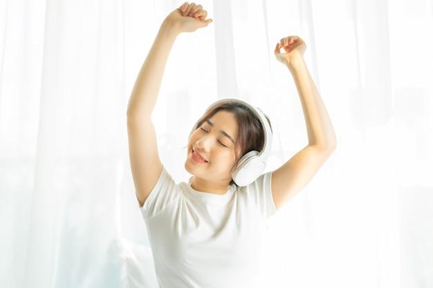Giovane ragazza seduta a letto ascoltando musica divertente
