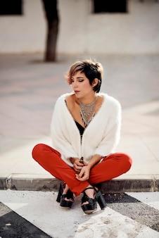 Giovane ragazza seduta sul pavimento tutta vestita di fumare un vapper