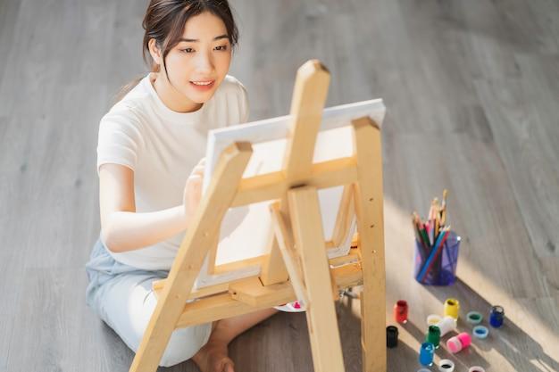 Ragazza che si siede sul pavimento che impara a disegnare da sola