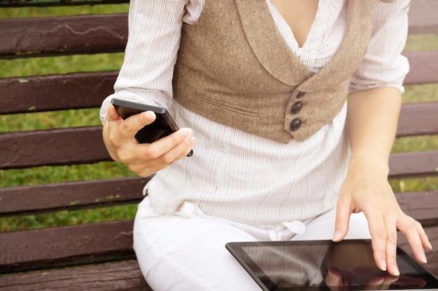 Giovane ragazza seduta all'aperto su una panchina con il suo tablet e telefono cellulare in mano